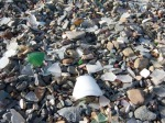 Up close, this rocky beach is littered w/ocean worn fragments of bottles, dishes & detritus.